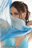 The girl with foulard. Close up portrairt of a pretty brunette with blue-sky earring playing to hide her face with a summer headscarf Stock Images