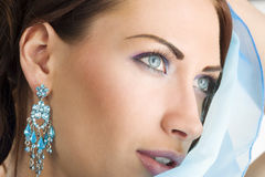 The girl with foulard. Close up portrairt of a pretty brunette with blue-sky earring playing to hide her face with a summer headscarf Stock Photos