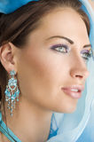 The girl with foulard. Close up portrairt of a pretty brunette with blue-sky earring playing to hide her face with a summer headscarf Stock Photography