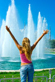 Girl and fountain. Blonde girl standing in front of the fountain royalty free stock photography