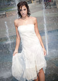 Girl in Fountain. A girl in a white dress walking through a fountain Stock Image