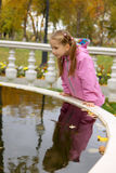The girl at fountain. The curious girl looks in fountain in autumn park stock image