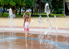 The girl and a fountain. The girl bathes in a fountain in hot day Stock Photos