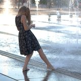 The girl at the fountain. Girl teenager pampering at the fountain in a summer sunny day royalty free stock photography