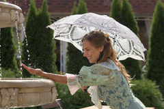 Girl at the fountain with white umbrella royalty free stock images