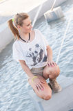 Girl by a Fountain. Young blonde girl posing by the fountain Royalty Free Stock Photography