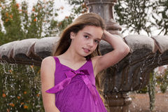 Girl by a Fountian in Purple Royalty Free Stock Photo