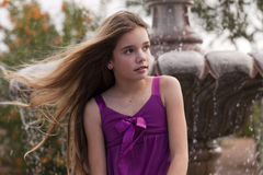 Girl by a Fountian in Purple with hair blowing Stock Photography