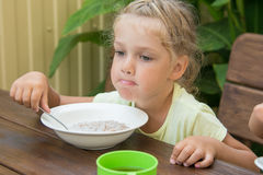 Girl of four years at a table outdoors thoughtfully eating porridge Stock Photos