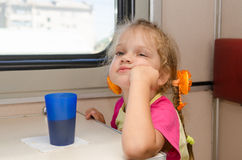 Girl of four years of thoughtful and tired of sitting on the train at the table on the side a place reserved seat Royalty Free Stock Photos