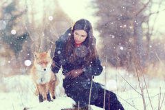 Girl with fox in winter forest stock images