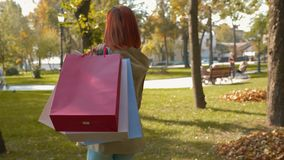 A girl with foxy hair walks through the park with purchases in multi-colored paper bags stock video footage