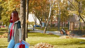 A girl with foxy hair walks through the park with purchases in multi-colored paper bags stock video