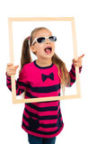 Girl and a Frame. Pretty little girl in sunglasses looking through empty wooden frame, making funny face expression, isolated royalty free stock images