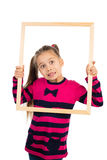 Girl and a Frame. Pretty little girl looking through empty wooden frame, making funny face expression, isolated stock photos