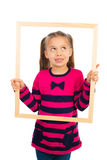 Girl and a Frame. Pretty little girl looking through empty wooden frame, making funny face expression, isolated stock image
