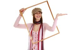 Girl and frame. Pretty girl in the big frame and cap Royalty Free Stock Photography