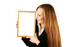 The girl with a framework. The girl looks at a wooden framework Stock Photos