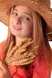 Girl with the freckles and straw hat holding in his hand a  whe Stock Images