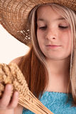 Girl with the freckles and straw hat holding in his hand a  whea Royalty Free Stock Photography