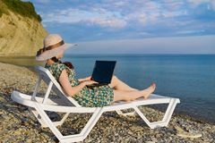 The girl is a freelancer, enjoying the beautiful, open sea.sitting on a sun lounger next to your laptop. the view from the back stock photos
