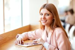Girl freelancer holding a tablet in the cafe.  royalty free stock photo