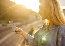 Girl freelancer at sunset speaks on the phone and works.  royalty free stock photo