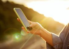 Girl freelancer at sunset speaks on the phone and works, blurred. Frame stock photography