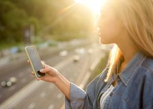 Girl freelancer at sunset speaks on the phone and works.  stock photography