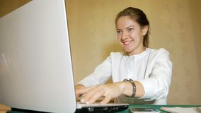 Girl freelancer by two hands very quickly typing on the laptop and looks very actively at the monitor. The young woman. The girl freelancer by two hands very stock video