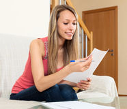 Girl freelancer working with documents. Successful girl freelancer working with documents at home royalty free stock photos