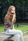 Girl freezes on a bench Stock Photos