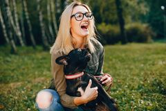 Girl with french bulldog. Pretty girl standing in a summer park. Woman with dog. Blonde in a glasses stock images
