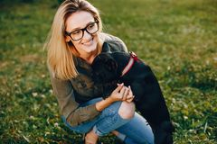 Girl with french bulldog. Pretty girl standing in a summer park. Woman with dog. Blonde in a glasses royalty free stock photography