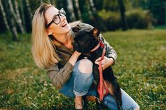 Girl with french bulldog. Pretty girl standing in a summer park. Woman with dog. Blonde in a glasses royalty free stock photos