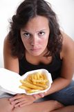 Girl with french fries. A young girl sitting and holding up a box of french fries Stock Photos