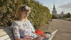 Girl in the fresh air typing on the keyboard of a white laptop. Young sophisticated woman using a laptop outdoors. stock footage