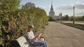 Girl in the fresh air typing on the keyboard of a white laptop. Young sophisticated woman using a laptop outdoors. stock video