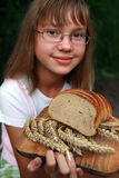Girl with fresh bread. Young smiling girl and fresh loaf of bread with wheat on wooden chopping board Royalty Free Stock Photo