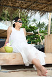 Girl with fresh coconut at a tropical beach resort Royalty Free Stock Photography