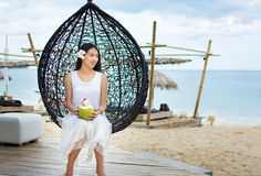 Girl with fresh coconut at a tropical beach resort Royalty Free Stock Images