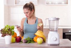 Girl with fresh fruit at kitchen table stock image