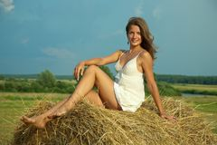 Girl  on fresh straw Stock Photo