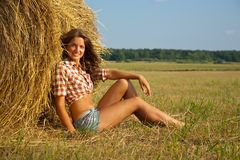 Girl on fresh straw Stock Image