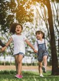 Girl and friend holding hands walking royalty free stock photography