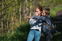 Girl friend points a finger somewhere. Two sisters having fun outdoors Stock Photo