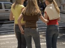 Girl Friends. Three good friends are waiting at an intersection in the city stock photo
