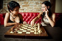 Girl-friends. Two pretty girl-friends friends playing chess Stock Photography