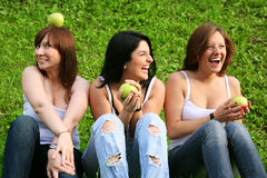 Girl friends with apples ourdoor. On green grass royalty free stock photo