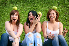 Girl friends with apples in the park. On the grass royalty free stock images